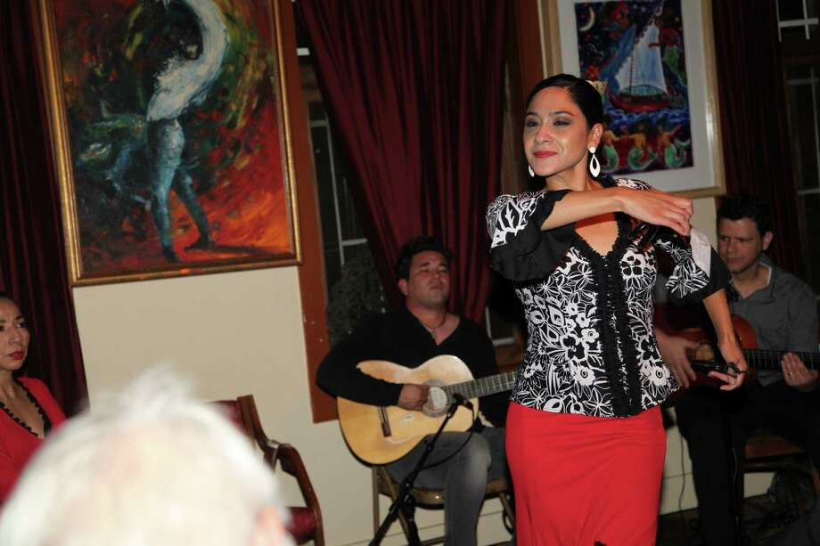 Jackie Rodriguez dances as Steve Arispe and Luis Linares play guitar.