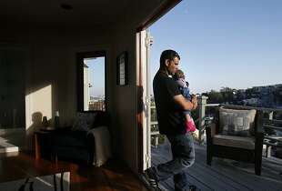 Kevin Frank carries his daughter during an open house 45 Deming St. in San Francisco, Calif. on Sunday, Nov. 10, 2013.