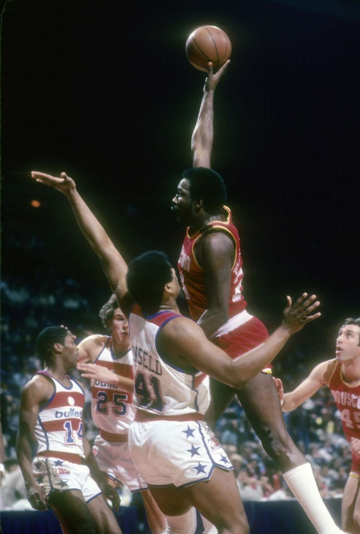 Moses Malone #24 of the Houston Rockets shoots over Wes Unseld #41 of the Washington Bullets during an NBA basketball game circa 1977 at the Baltimore Civic Center in Baltimore, Maryland. Malone played for the Rockets from 1976-82. (Photo by Focus on Sport/Getty Images)