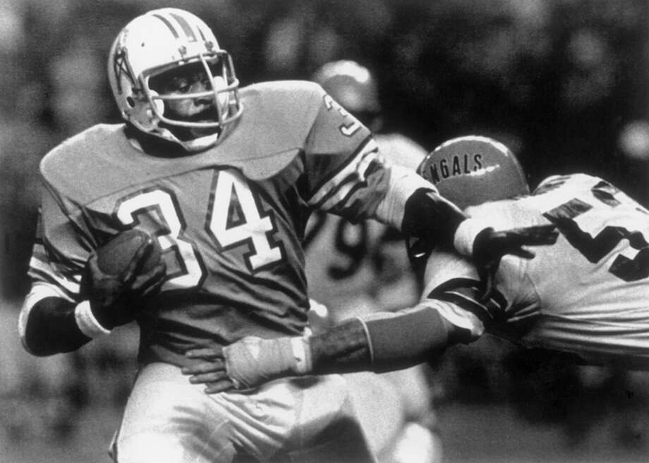 Running back Earl Campbell #34 of the Houston Oilers pushes aside Cincinnati Bengal linebacker Bo Harris during a game on November 19, 1979 in Houston Texas. The Oilers won 42- 21. (Photo by Bruce Bennett Studios/Getty Images) Photo: B Bennett, Getty Images / 1970 Bruce Bennett Studios