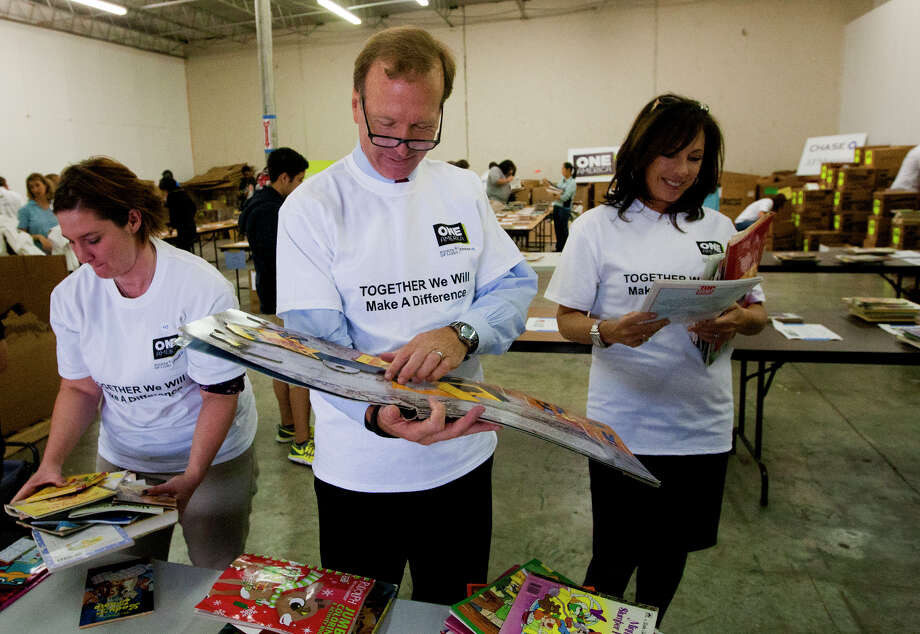 Shannon Keyes, left, Neil Bush, center, and Lois Backon, right, sort through books at the Books Between Kids warehouse as 40 volunteers sorted through 7,000 books, Tuesday, Nov. 12, 2013, in Houston. Neil and Barbara Bush presented Books Between Kids, the Houston non-profit that gives books to disadvantaged students, with the Daily Point of Light Award. Last year, the start-up organization collected and distributed more than 100,000 books to to kids enrolled at 22 Houston schools. The Barbara Bush Houston Literacy Foundation also extended Books Between Kids a grant to match donations up to $9,000, to support the annual lease of the warehouse where the books are stored before distribution. (Cody Duty / Houston Chronicle) Photo: Cody Duty, Staff / © 2013 Houston Chronicle
