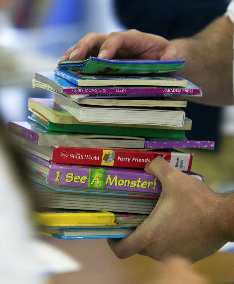 Steven Brown carries a stack of books to be boxed at the Books Between Kids warehouse as 40 volunteers sorted through 7,000 books, Tuesday, Nov. 12, 2013, in Houston. Neil and Barbara Bush presented Books Between Kids, the Houston non-profit that gives books to disadvantaged students, with the Daily Point of Light Award. Last year, the start-up organization collected and distributed more than 100,000 books to to kids enrolled at 22 Houston schools. The Barbara Bush Houston Literacy Foundation also extended Books Between Kids a grant to match donations up to $9,000, to support the annual lease of the warehouse where the books are stored before distribution. (Cody Duty / Houston Chronicle) Photo: Cody Duty, Staff / © 2013 Houston Chronicle