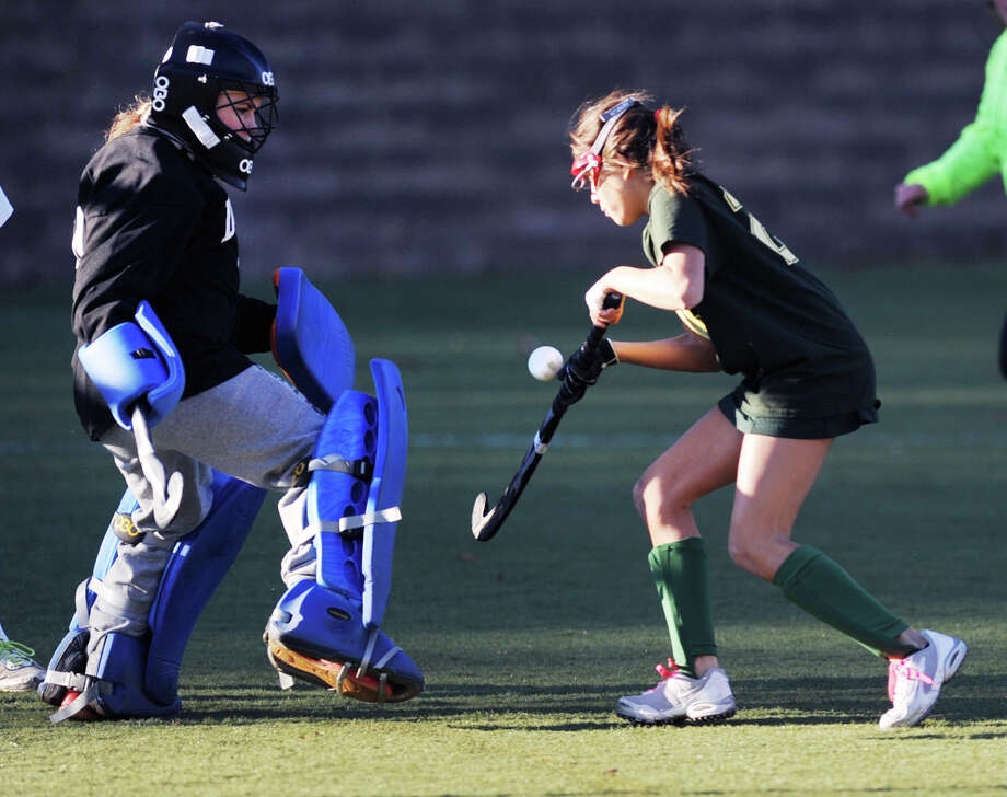 At right, Tati Viola (# 21) of Greenwich Academy plays a rebound that is being defended by Deerfield goalie Katherine Heaney, left, during the girls high school field hockey playoff game between Greenwich Academy and Deerfield Academy at Greenwich, Wednesday afternoon, Nov. 13, 2013. Viola did not score on the play. Photo: Bob Luckey / Greenwich Time
