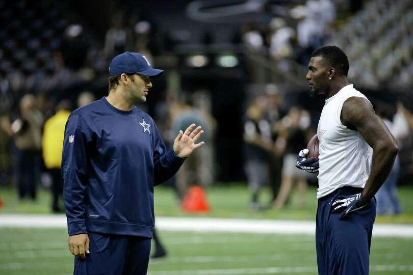 Dallas Cowboys quarterback Tony Romo, left, talks with wide receiver Dez Bryant before an NFL footba