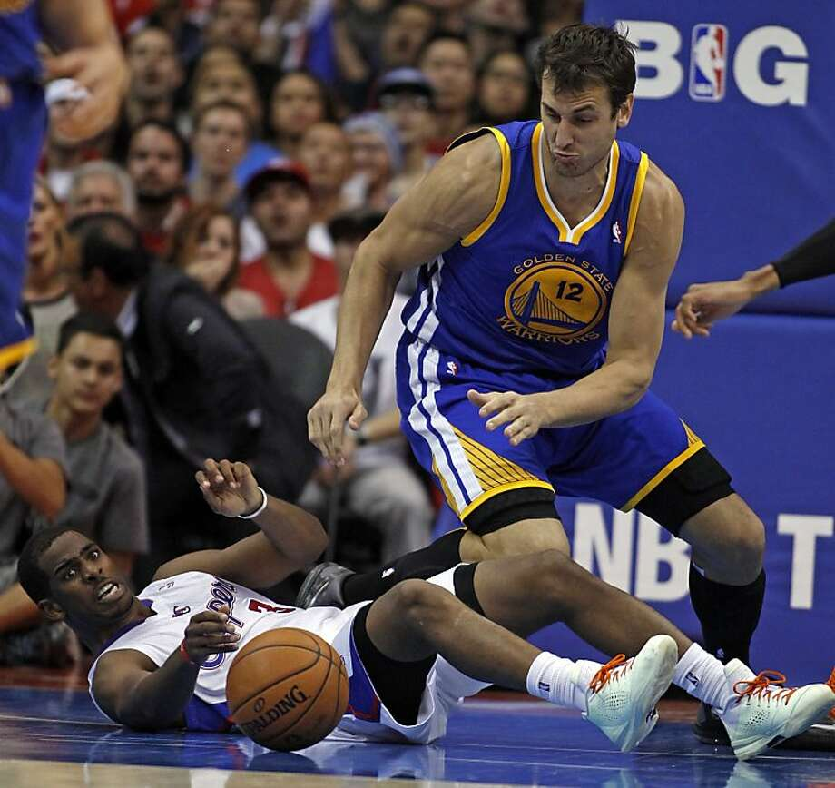 The Clippers' Chris Paul (on ground) and the Warriors' Andrew Bogut go for the ball in a Halloween game. Photo: Alex Gallardo, Associated Press