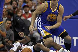 Los Angeles Clippers guard Chris Paul, left, battles Golden State Warriors center Andrew Bogut (12), of Australia, for the ball in the fourth quarter during an NBA basketball game on Thursday, Oct. 31, 2013, in Los Angeles. The Clippers won the game 126-115.  (AP Photo/Alex Gallardo)