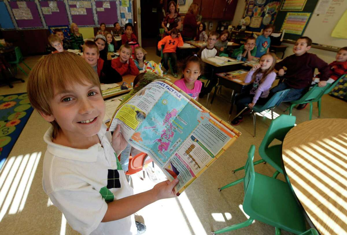 Carter Tripp, 8, stands in front of his classmates as he holds a map of the Philipines at the Duanesburg Elementary School Wednesday afternoon Nov. 13, 2013 in Duanesburg, N.Y. Carter started a fundraiser, Carter Cares for Children, with the help of his mother, Nicole, to aid the victims of Super Typhoon Haiyan in the Philippines. Carter's 75-year-old grandfather, Ron Welton, lives just outside of Maasin, a city about 60 miles from Tacloban, the hardest hit area in the Philippines. (Skip Dickstein/Times Union