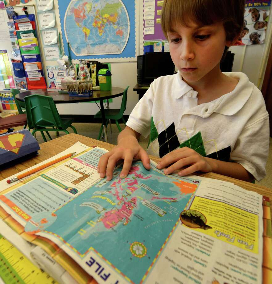 Carter Tripp, 8, checks out a map of the Philipines at the Duanesburg Elementary School Wednesday afternoon Nov. 13, 2013 in Duanesburg, N.Y.  Carter started a fundraiser, Carter Cares for Children, with the help of his mother, Nicole, to aid the victims of Super Typhoon Haiyan in the Philippines.  Carter's 75-year-old grandfather, Ron Welton, lives just outside of Maasin, a city about 60 miles from Tacloban, the hardest hit area in the Philippines.     (Skip Dickstein/Times Union Photo: SKIP DICKSTEIN / 00024630A
