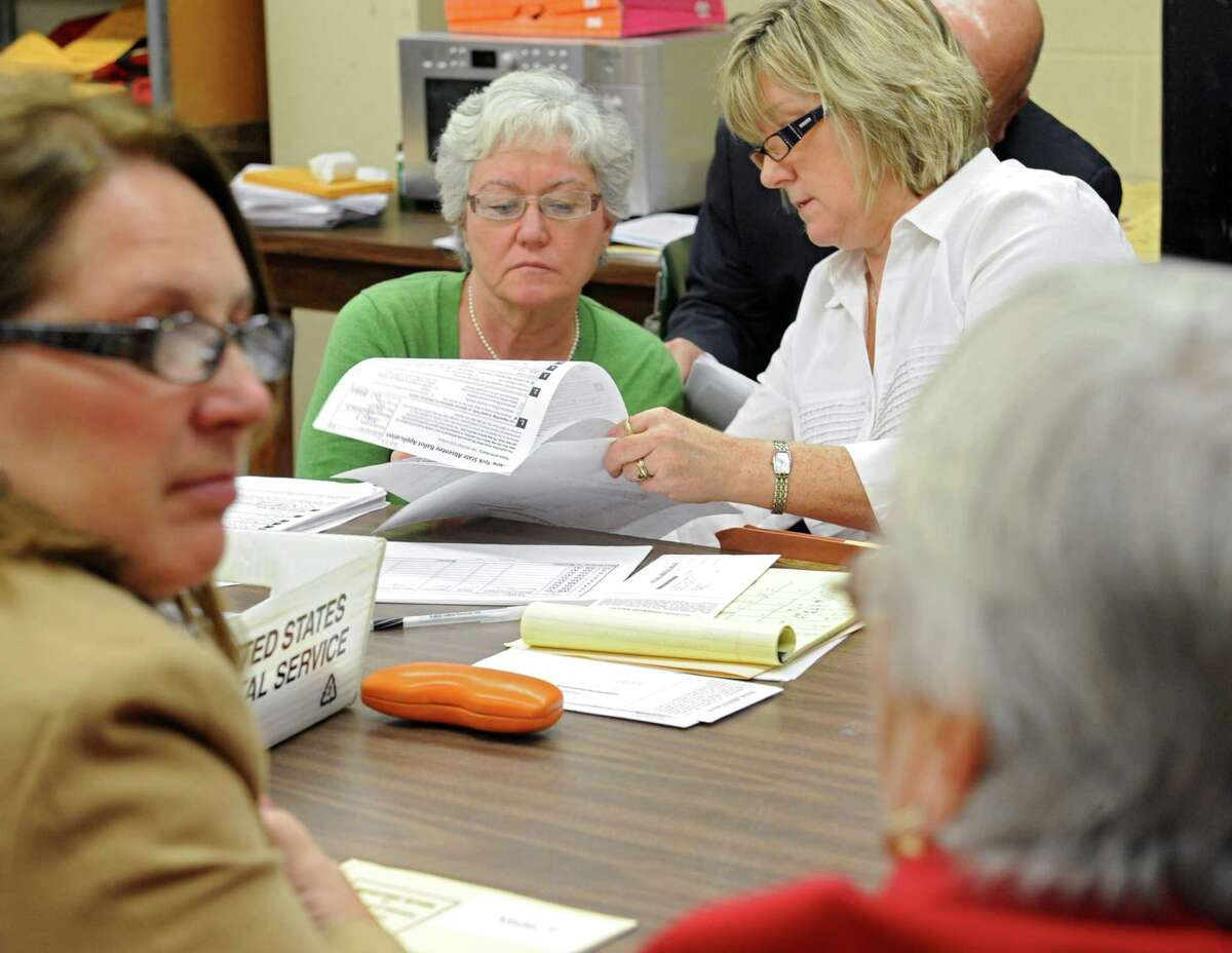 Democratic candidate for Town Supervisor Cynthia Young, second from left, looks over absentee ballots with Kathleen O'Keefe, attorney hired by the democratic party, while Donna Gundersen, left, democratic senior clerk and Cindy Wade, republican senior clerk, right, talk at the Saratoga County Board of Elections on Wednesday, Nov. 13, 2013 in Malta, N.Y. Young is in a tight race with incumbent Paul Sausville for Malta town supervisor. (Lori Van Buren / Times Union)