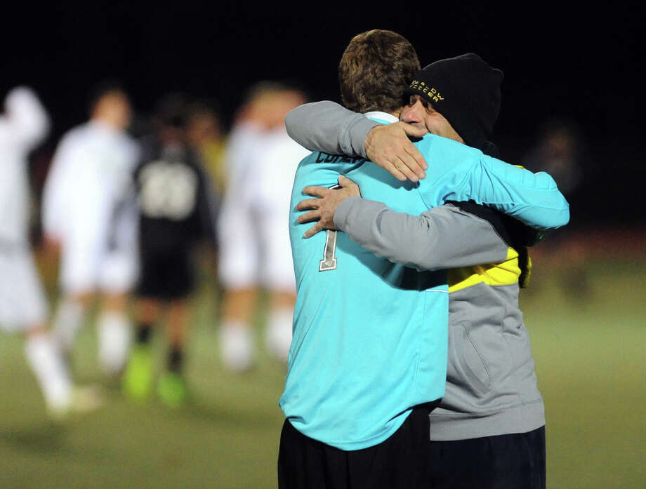Joel Barlow Assistant Coach Mark Nizzardo hugs goalie Peter Cohen after the team defeat Daniel Hand High School, during Class L boys soccer state semifinal action in Hamden, Conn. on Wednesday November 12, 2013. Photo: Christian Abraham / Connecticut Post