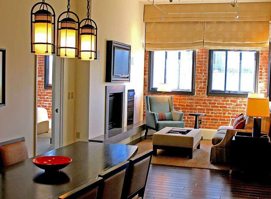 A brick wall accents the living room, which includes a built-in entertainment center. Photo: Fairmont Heritage Place