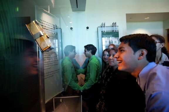 A gold ingot brings a glow to the face of Ricardo Gomez, a Sam Rayburn High School senior on a tour of the bank Wednesday.