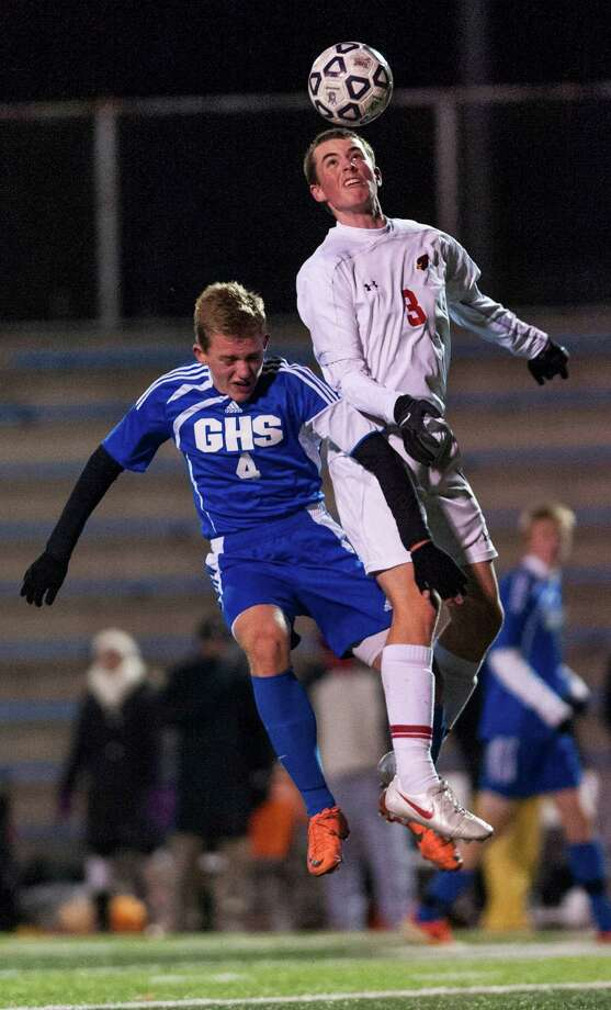 Glastonbury high school's Brock Hassett and Greenwich high school's Nicholas Bartels go up to head the ball during a CIAC semifinal boys soccer tournament game played at West Haven high school, West Haven, CT on Wednesday, November, 13th, 2013. Photo: Mark Conrad / Connecticut Post Freelance