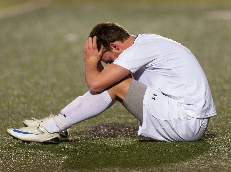 Greenwich high school's Will Gittings sits dejected on the field after losing to Glastonbury high school in a CIAC semifinal boys soccer tournament game played at West Haven high school, West Haven, CT on Wednesday, November, 13th, 2013. Photo: Mark Conrad / Connecticut Post Freelance