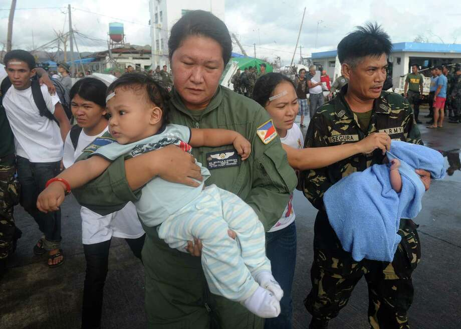 Soldiers carry the babies of typhoon survivor Lina Mimbrello (C), 28, two week old baby Joseph (R) and one year old Justin (L), before they take a flight on a C-130 military plane out of Tacloban, Leyte province, central Philippines Tacloban, Leyte province, central Philippines on November 13, 2013.  The US military has ordered two amphibious ships to the Philippines to help victims of the devastating Typhoon Haiyan and a third was poised to deploy, officials said.  AFP PHOTO/NOEL CELISNOEL CELIS/AFP/Getty Images Photo: NOEL CELIS / AFP