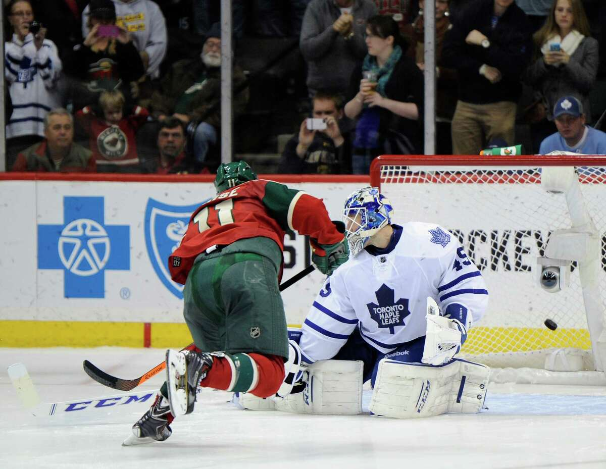 ST PAUL, MN - NOVEMBER 13: Zach Parise #11 of the Minnesota Wild scores a goal on Jonathan Bernier #45 of the Toronto Maple Leafs during the shootout of the game on November 13, 2013 at Xcel Energy Center in St Paul, Minnesota. The Wild defeated the Maple Leafs 2-1 in a shootout. (Photo by Hannah Foslien/Getty Images) ORG XMIT: 181110655