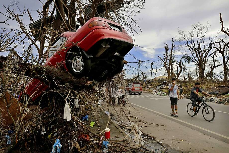 TACLOBAN, PHILIPPINES - NOVEMBER 13:  Residents walk past scenes of devastation in the aftermath of Typhoon Haiyan on November 13, 2013 in Tacloban, Leyte, Philippines. Typhoon Haiyan, packing maximum sustained winds of 195 mph (315 kph), slammed into the southern Philippines and left a trail of destruction in multiple provinces, forcing hundreds of thousands to evacuate and making travel by air and land to hard-hit provinces difficult. Around 10,000 people are feared dead in the strongest typhoon to hit the Philippines this year. (Photo by Kevin Frayer/Getty Images)  *** BESTPIX *** Photo: Kevin Frayer, Getty Images