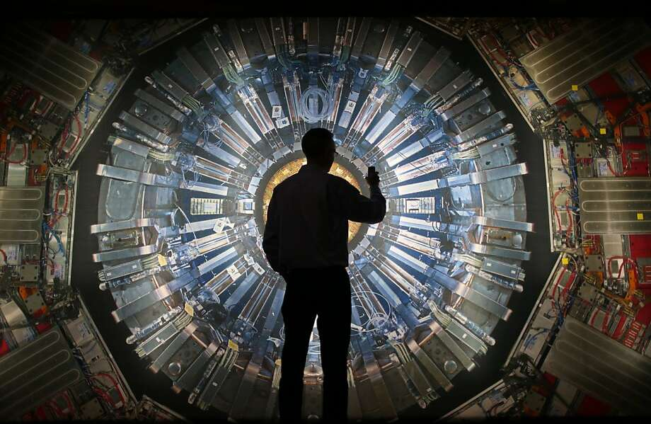 LONDON, ENGLAND - NOVEMBER 12:  A visitor takes a phone photograph of a large back lit image of the Large Hadron Collider (LHC) at the  Science Museum's 'Collider' exhibition on November 12, 2013 in London, England. At the exhibition, which opens to the public on November 13, 2013  visitors will see a theatre, video and sound art installation and artefacts from the LHC, providing a behind-the-scenes look at the CERN particle physics laboratory in Geneva. It touches on the discovery of the Higgs boson, or God particle, the realisation of scientist Peter Higgs theory.  (Photo by Peter Macdiarmid/Getty Images)  *** BESTPIX *** Photo: Peter Macdiarmid, Getty Images