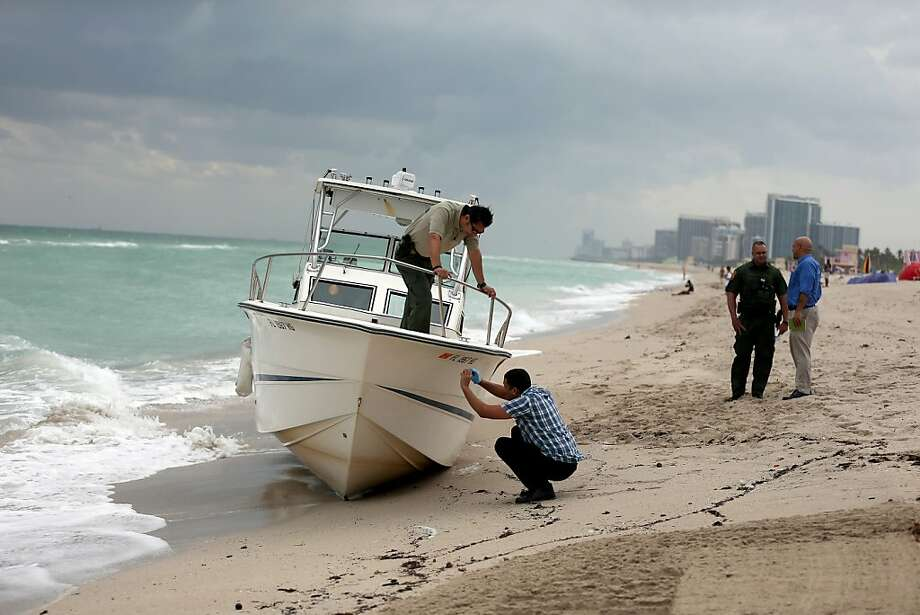 BAL HARBOUR, FL - NOVEMBER 13:  Border Patrol agents investigate a boat that was found washed ashore on Haulover Beach on November 13, 2013 in Bal Harbour, Florida.  The Border Patrol were investigating whether migrants may have been on board.  (Photo by Joe Raedle/Getty Images) Photo: Joe Raedle, Getty Images
