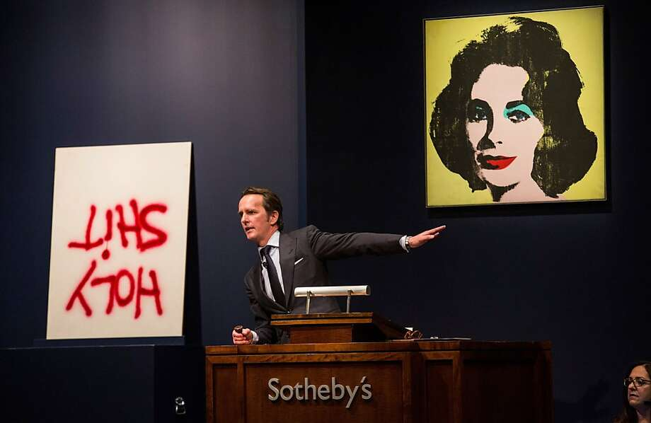 "NEW YORK, NY - NOVEMBER 13: Dan Colen's artwork titled, ""Holy Shit"" is auctioned at Sotheby's for $341,000 on November 13, 2013 in New York City. The big seller of the night was Andy Warhol's artwork, ""Silver Car Crash (Double Disaster)"" which sold for $104,445,000, a record for the famed artist. Andy Warhol's artwork titled ""Liz #1 (Early Colored Liz)"" is displayed on the right. (Photo by Andrew Burton/Getty Images) Photo: Andrew Burton, Getty Images"