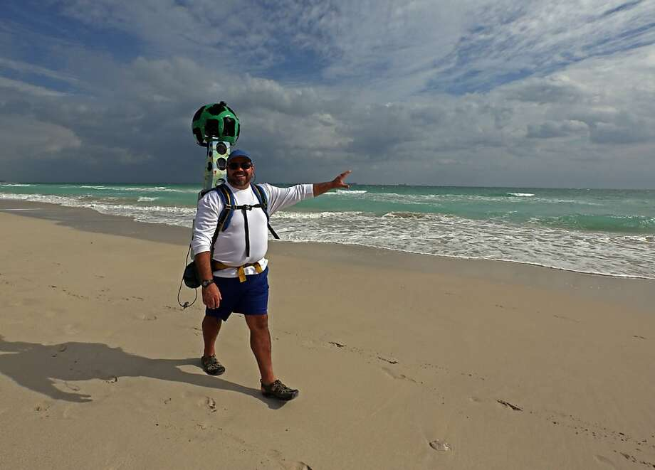 Trekker Gregg Matthews, wearing a special Google-designed camera, completes the last mile of the Google Maps project to capture 360-degree images of Florida's 825 miles of beaches Wednesday, Nov. 13, 2013, in Miami Beach, Fla. The state's tourism and marketing arm, Visit Florida, said the journey began in July, with two-person teams trained by Google Map experts to capture the images. (AP Photo/The Miami Herald, Walter Michot)  MAGS OUT Photo: Walter Michot, Associated Press