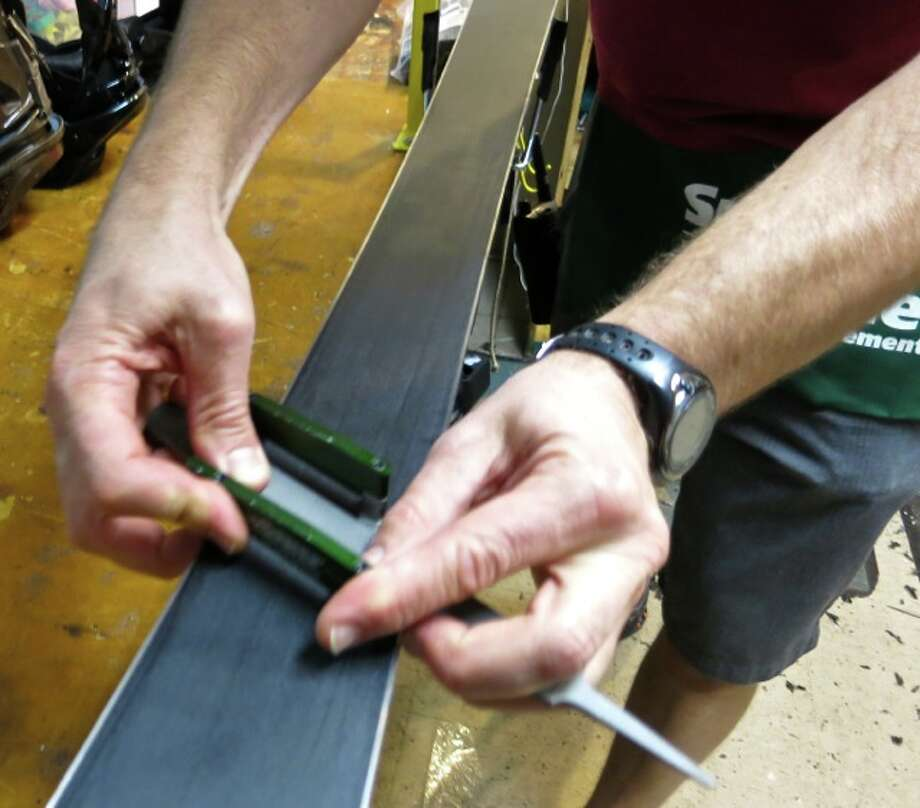 Another shot of hand sharpening the ski. Photo: Jules Older, Special To The Chronicle