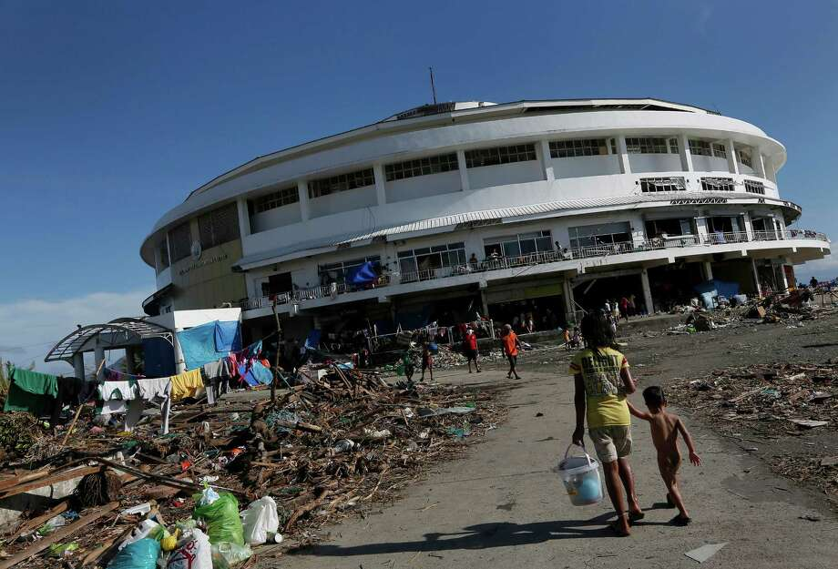 A young girl walks her brother to the Tacloban City Convention Center known as the Astrodome Thursday, Nov. 14, 2013, where hundreds of displaced typhoon survivors have set up makeshift shelters throughout the complex's once bustling shops and popular basketball court. For the thousands of people jamming the Tacloban City Astrodome, the great halls with a solid roof was a heaven-sent refuge when Typhoon Haiyan rammed eastern Philippines on Friday. Evacuated from their homes along the coast in time, they had a place to hide from the furious winds and gigantic water surge. But along with shelter, their constant companion now is misery and hunger. Photo: Vincent Yu, AP / AP