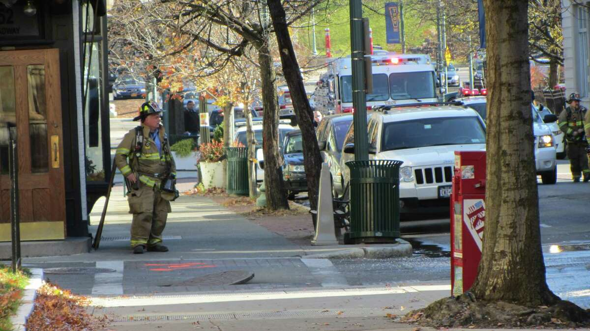 A firefighter works near the scene of a manhole cover explosion that forced Troy officials to evacuate buildings on Broadway, including the city's main post office. (Bob Gardinier / Times Union)