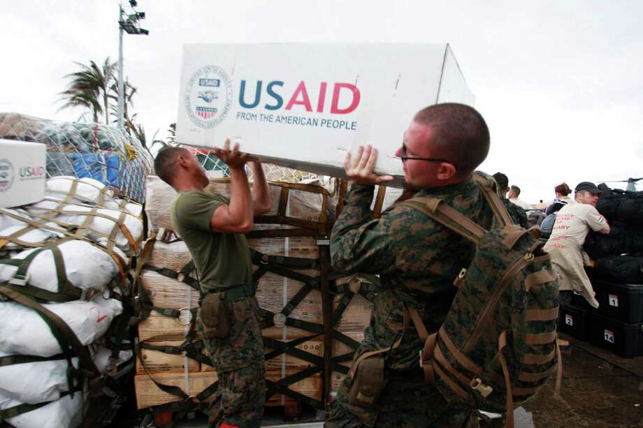 US troops prepare relief supplies for distribution to survivors of Typhoon Haiyan on November 14, 2013 in Tacloban, Leyte, Philippines. Typhoon Haiyan which ripped through Philippines over the weekend has been described as one of the most powerful typhoons ever to hit land, leaving thousands dead and hundreds of thousands homeless. Countries all over the world have pledged relief aid to help support those affected by the typhoon, however damage to the airport and roads have made moving the aid into the most affected areas very difficult. With dead bodies left out in the open air and very limited food, water and shelter, health concerns are growing. Photo: Jeoffrey Maitem, Jeoffrey Maitem/Getty Images / 2013 Getty Images