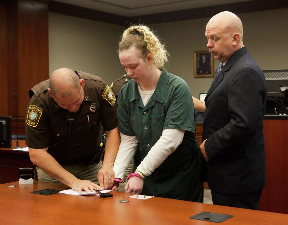 Abigail Catt, center, and her attorney David Michael Ryan, right, stand before Judge Clifford Vacek in the 400th District Court, Thursday, Nov.14, 2013 in Richmond, Tx. Deputy Scott Rodriguez applies her fingerprint to court documents after Catt agreed to a five year prison term for her part in committing several robberies along with her father Ronald Scott Catt and brother Hayden Catt in the Fort Bend County area.(Bob Levey/For The Chronicle) Photo: Bob Levey, Houston Chronicle / ©2013 Bob Levey