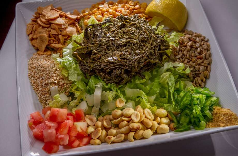 The Tea Leaf Salad: Oil-soaked green tea leaves atop sliced romaine, surrounded by fried garlic slices, peanuts, sesame seeds, fried yellow beans, tomatoes, jalapenos and dried shrimp. Photo: John Storey, Special To The Chronicle
