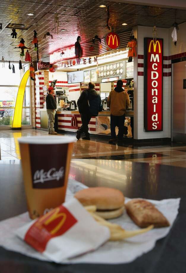 DES PLAINES, IL - OCTOBER 24:  In this photo illustration, customers order food from a McDonald's restaurant on October 24, 2013 in Des Plaines, Illinois. McDonald's has announced it will make changes to its low-priced Dollar Menu, which includes items like coffee, small fries, hamburgers and apple pies. The new menu, dubbed the Dollar Menu and More, will offer some higher priced options such as the grilled Onion Cheddar Burger and a McChicken sandwich.  (Photo Illustration by Scott Olson/Getty Images) Photo: Getty Images