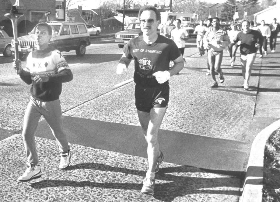 Guierno Mayloire carries the Special Olympics torch alongside Stamford Police Capt. Steve Devito as they run along city streets on Nov. 18, 1988. Photo: File Photo, Advocate / Advocate