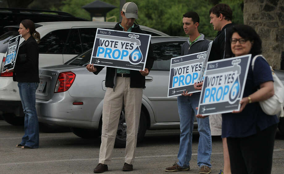 Supporters of Proposition 6 hold signs during early voting. Now that the amendment to fund water projects has passed, Texans should get involved in the regional water planning process. Photo: John Davenport / San Antonio Express-News