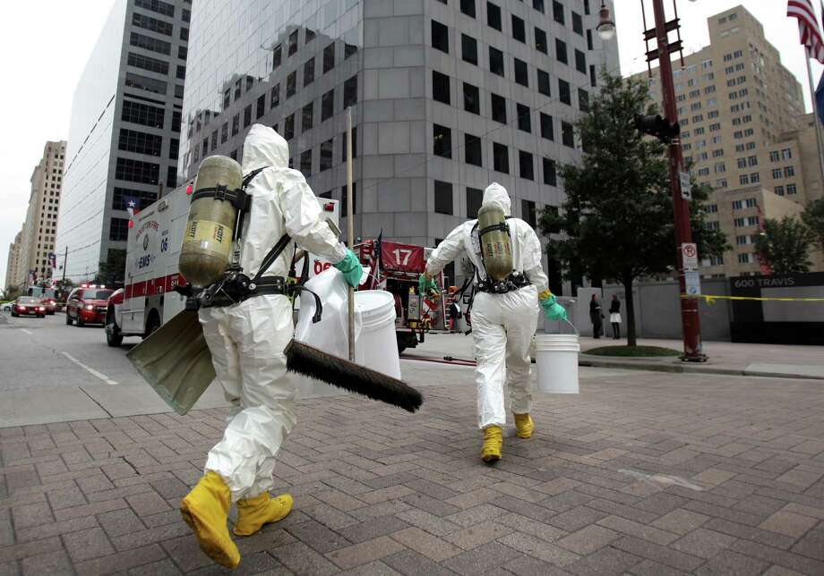 HFD Hazardous Materials prepare to enter the Chase Parking Garage to remove Glutaraldehyde, a cleaning chemical, from work area inside the building on Thursday, Nov. 14, 2013, in Downtown Houston. HFD Hazardous Materials unit was called to the scene after the glutaraldehyde container lid pops off and exposes two workers. No evacuation was in acted or additional injuries. Photo: Mayra Beltran, Houston Chronicle / © 2013 Houston Chronicle