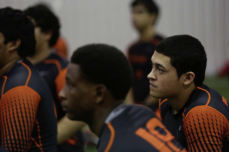 Refugio High School quarterback Travis Quintanilla kneels with his teammates as a coach talks to them before practice at the school in Refugio on Thursday, Nov. 14, 2013. Photo: Lisa Krantz, San Antonio Express-News / San Antonio Express-News