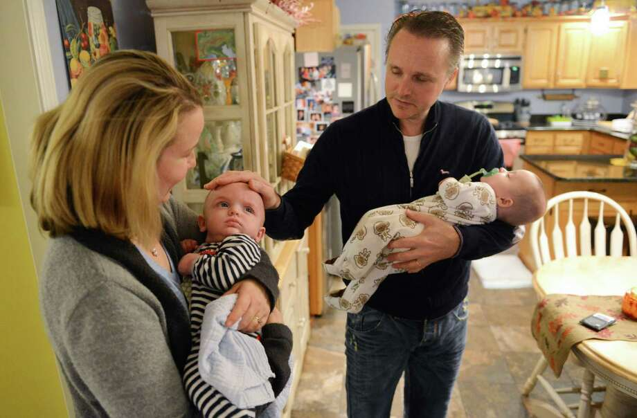 Janelle and Rory Mason hold their twin boys, Dylan, left, and Paul, in their home in Newtown, Conn. on Tuesday, Nov. 12, 2013. Janelle and Rory had been trying to conceive or adopt for 15 years without any success. Janelle's friend, Jennifer LaCava, offered to be her surrogate to carry her children. The surrogacy was successful and the boys are now 4 months old. Photo: Tyler Sizemore / The News-Times