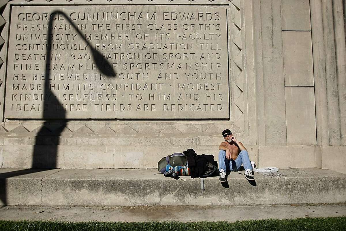 Self proclaimed urban camper Jonathan Dignes smokes as he soaks up some sun on the side of Edwards Stadium on the Cal campus in Berkeley, CA Wednesday, November 13, 2013.