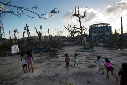 Children run toward a U.S. military aircraft as it arrives to distribute aid to Typhoon Haiyan survivors in Guiuan on Thursday. Aid was beginning to reach some of the half-million people displaced by Haiyan. Photo: David Guttenfelder, STF / AP