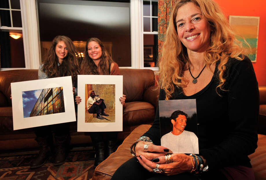 Carol Shwidock, right, holds a photo of her husband, Brad Shwidock, as their daughters, Samara, left, and Zoe, hold their favorite photos that their father took while posing for a photograph at their home in Stamford, Conn., on Thursday, Nov. 14, 2013. The family patriarch, Brad, died last November from primary sclerosing cholangitis, a disease of the liver. Though he was a dentist by day, he was an avid photographer who won awards in his free time. This Saturday, Brad's work will be shown at a one-day-only showing at Franklin Street Works in Stamford from 5-8 p.m. Photo: Jason Rearick / Stamford Advocate