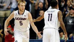 Connecticut's Niels Giffey, left, and Ryan Boatright celebrate a basket by Giffey during the first half of an NCAA college basketball game Thursday, Nov. 14, 2013, in Storrs, Conn.