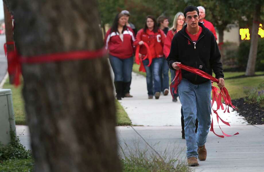 Jacob Stansel, a sophomore at Canyon High School carries ribbons as he helps members of Moms for New Braunfels tie red ribbons on trees and signs along Seguin St. in New Braunfels, TX for Canyon High School sophomore student Logan Davidson who was assaulted at school and later died of his injuries. Thursday, Nov. 14, 2013. Photo: Bob Owen, San Antonio Express-News / ©2013 San Antonio Express-News