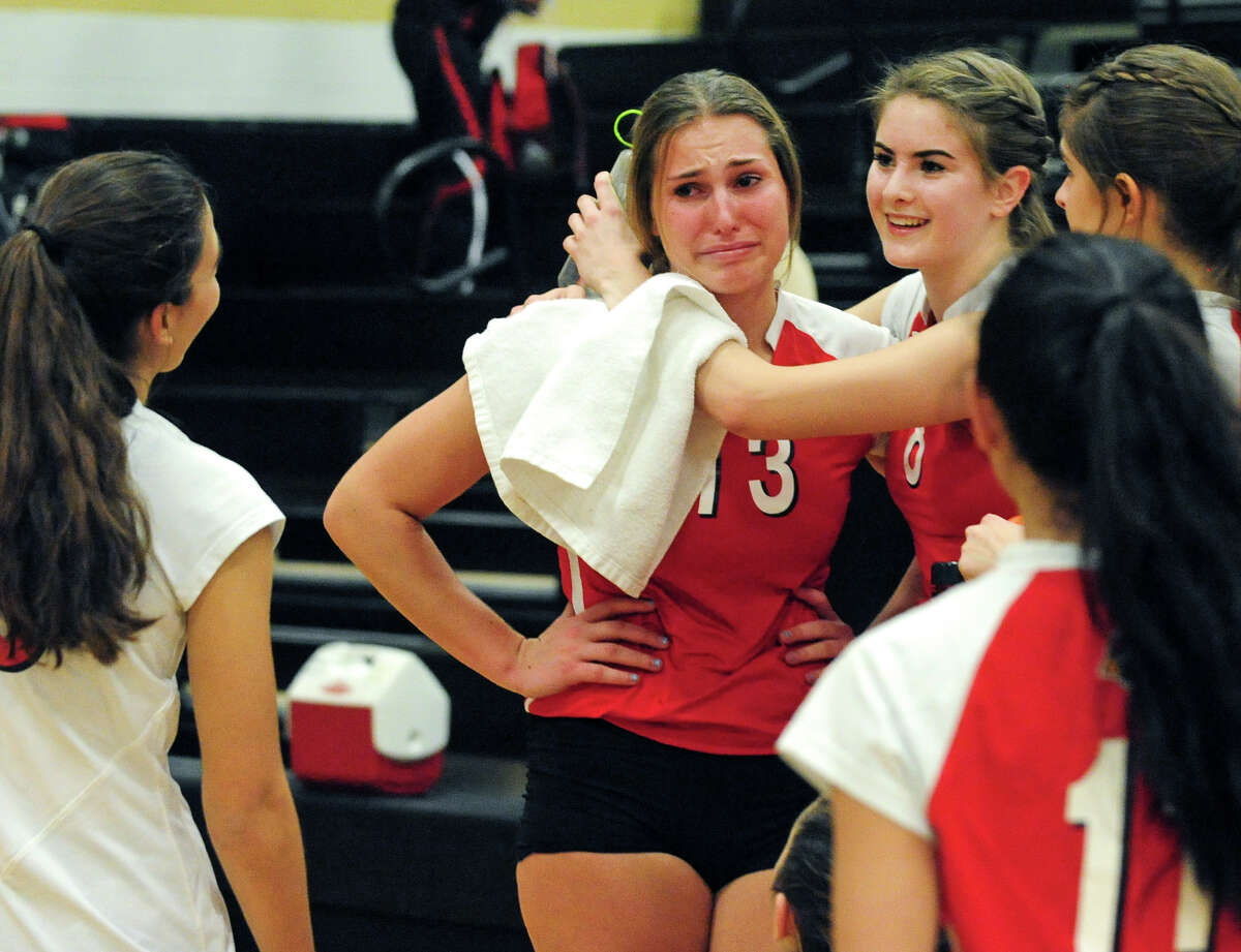 Greenwich's Heather Desino, center, gets a hug from teammate Jesse Schelz, at right, after the team's defeat by Staples, in Class LL girls volleyball semi-final action in Trumbull, Conn. on Thursday November 18, 2013.