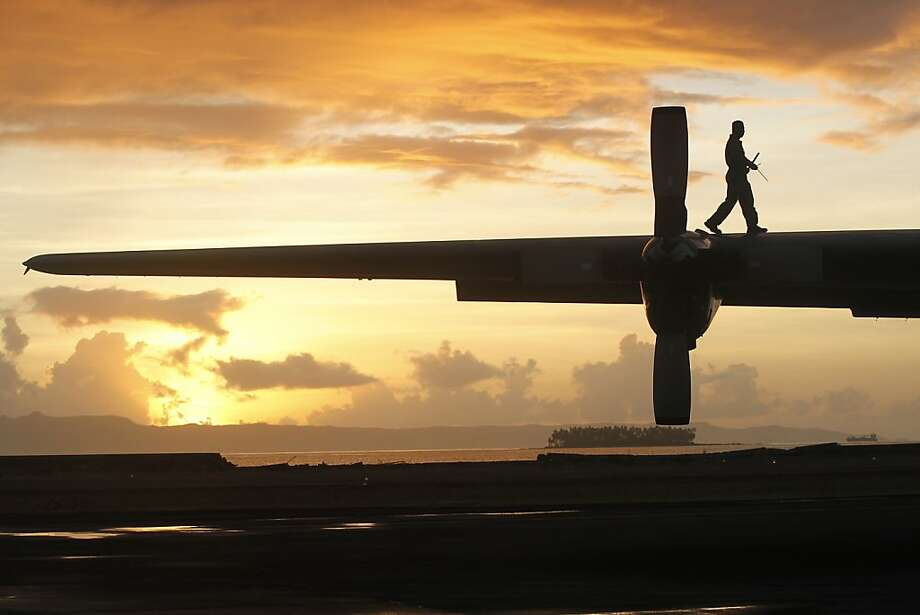 Wing inspection:A Philippine air crew member does pre-flight checks on a C-130 evacuation flight at the airport in Tacloban. Thousands displaced by Typhoon Haiyan have been trying to leave the ravaged city. Photo: Wally Santana, Associated Press