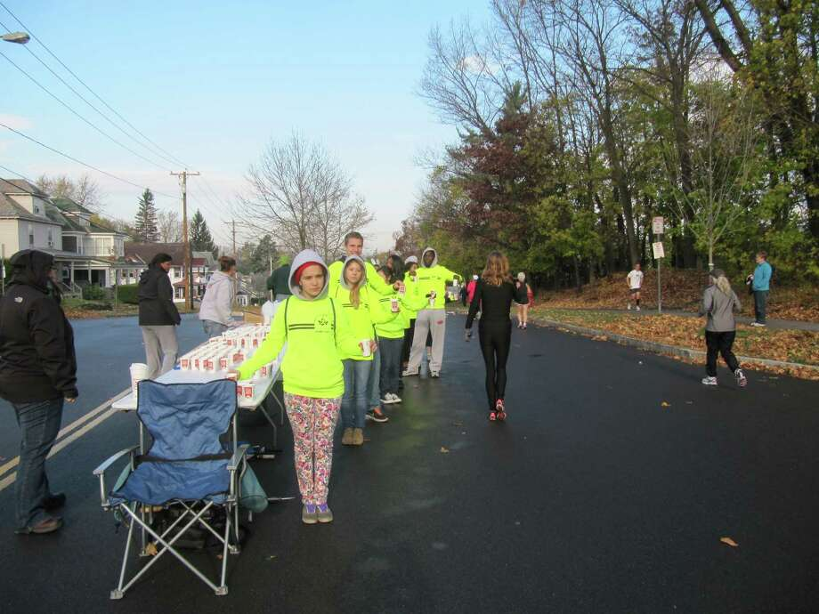 Photo by Gillian Scott. Volunteers hand out water at the Bradley Street water station during the 2012 Stockade-athon 15K road race. The Butryn family has been running the spot for more than a decade.