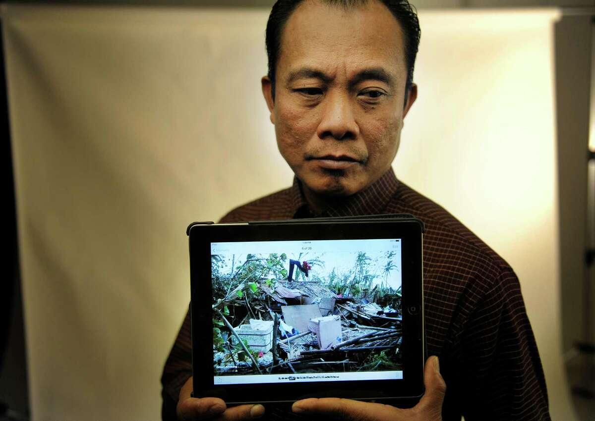 Nico Arrobang, of Latham, holds a tablet that displays a photograph of one of his relative's home in Roxas City, Philippines that was destroyed by the typhoon. Arrobang, who grew up in Roxas City in a home surrounded by relative's homes, said that his mother, sister and aunts and uncles in Roxas City have had their homes destroyed and have lost many of their belongings because of the storm. (Paul Buckowski / Times Union)