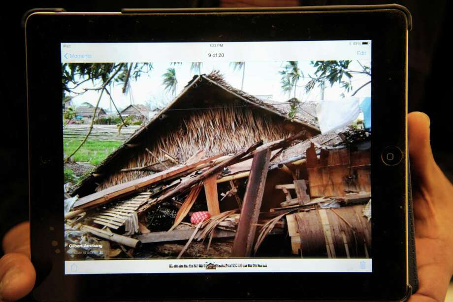 Nico Arrobang, of Latham, holds a tablet that displays a photograph of a relative's home in Roxas City, Philippines that was destroyed by the typhoon.  Arrobang, who grew up in Roxas City in a home surrounded by relative's homes, said that his mother, sister and aunts and uncles in Roxas City have had their homes destroyed and have lost many of their belongings because of the storm.   (Paul Buckowski / Times Union) Photo: Paul Buckowski / 00024643A