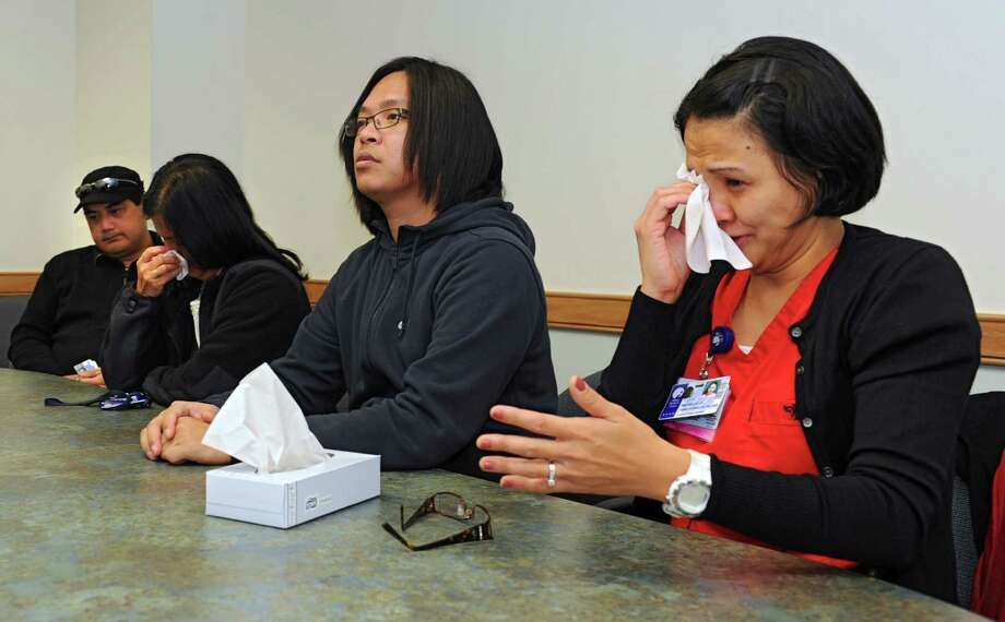 Michelle Tubis-Corrales, RN BSN at Albany Medical Center, right, gets emotional as she talks about how Typhoon Haiyan has affected her family back home in the Philippines during an interview at Albany Medical Center on Thursday, Nov. 14, 2013 in Albany N.Y. Case manager Gemma Lour Nayra,, second from left, with her  husband Rogeliio T.R. Nayra, left, and staff nurse Jesuit Paul Nugas, also told their stories of despair. (Lori Van Buren / Times Union) Photo: Lori Van Buren / 00024661A