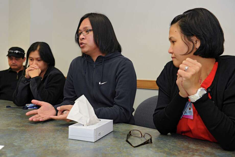 Staff nurse Jesuit Paul Nugas, second from right, talks about how Typhoon Haiyan has affected his family back home in the Philippines during an interview at Albany Medical Center on Thursday, Nov. 14, 2013 in Albany N.Y. Case manager Gemma Lour Nayra,, second from left, with her  husband Rogeliio T.R. Nayra, left, and Michelle Tubis-Corrales, RN BSN, right, also told their stories of despair. (Lori Van Buren / Times Union) Photo: Lori Van Buren / 00024661A