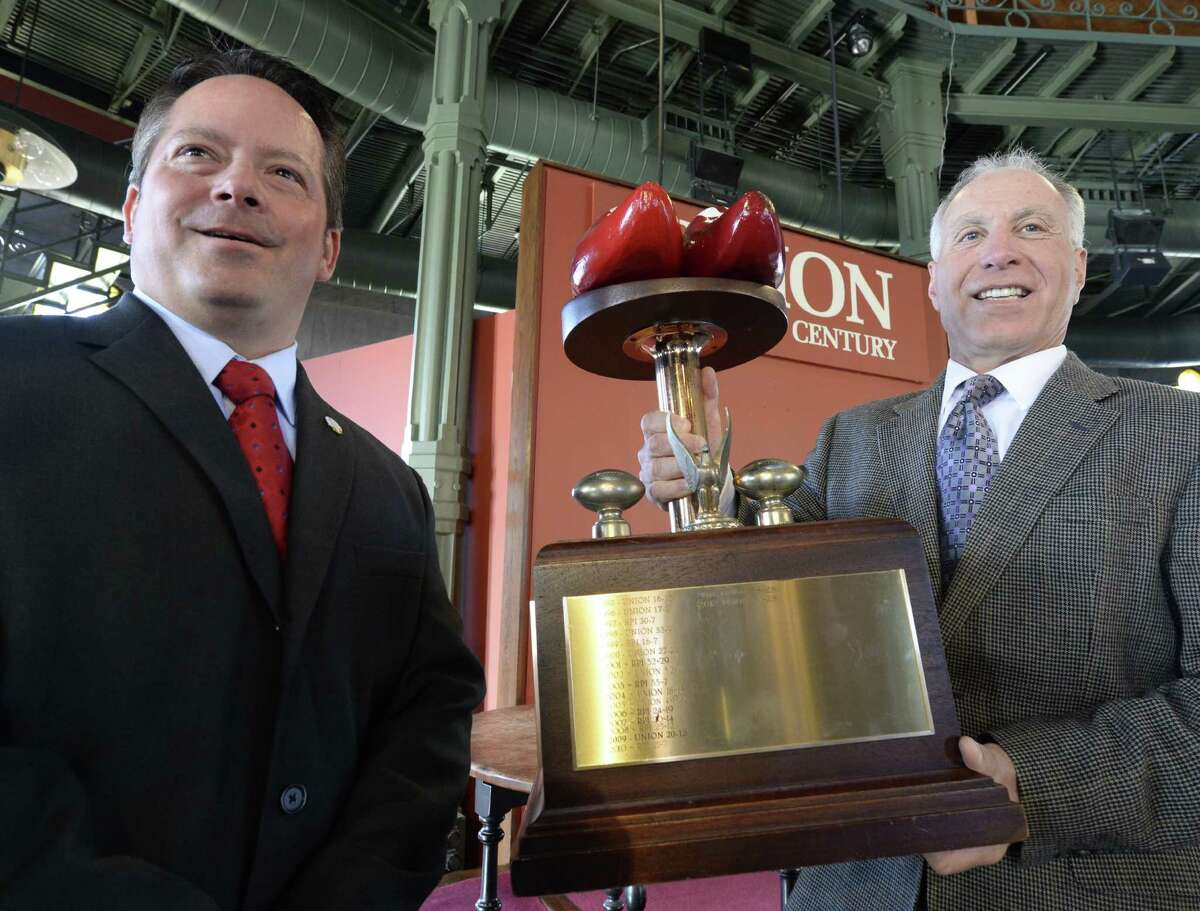 RPI Men's Football Coach Ralph Isernia, left stands with Union Men's Football Coach John Audino Thursday afternoon Nov. 14, 2013 on the Union College campus in Schenectady, N.Y. Audino holds the Dutchmen Shoe trophy which is given to the winning team after the game between Union and RPI. The game will be played this Saturday Nov. 16th. (Skip Dickstein / Times Union)